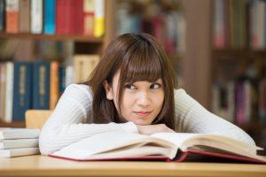 本を読みながら笑顔の女性