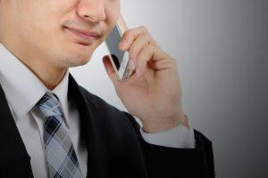 iPhoneで電話をする男性