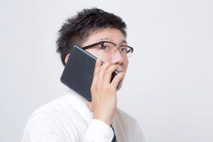 タブレットで電話をする男性