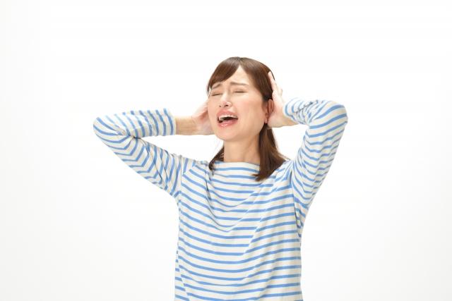 不安で頭を抱える女性
