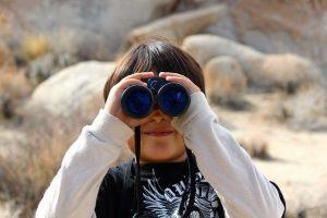 双眼鏡でなにかを探している少年