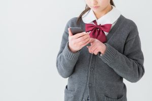 スマホを利用する中学生