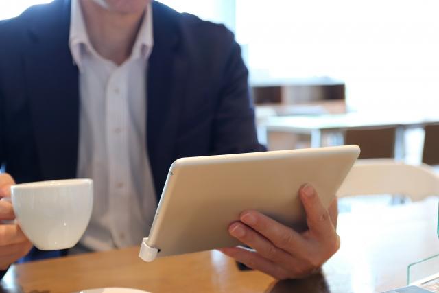 カフェでタブレットをみる男性