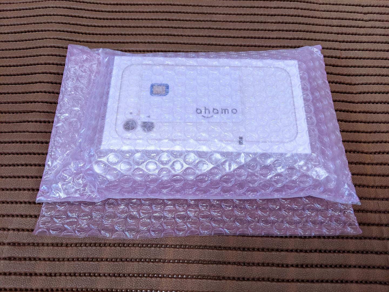 ahamoの箱に入っていたSIMカードとiPhone 11